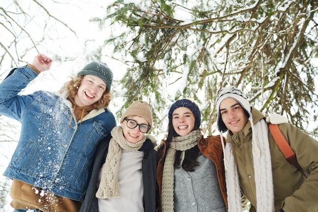 Amigos alegres en bosque de invierno