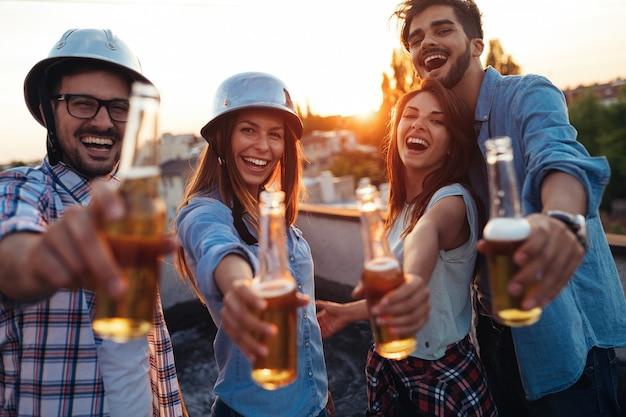 Amigos alegres felices pasando momentos divertidos juntos y bebiendo