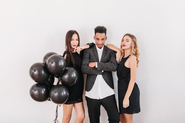 Amigos alegres con globos negros durante la fiesta en casa