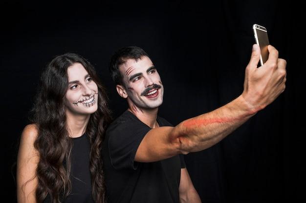 Amigos alegres haciendo selfie en teléfono
