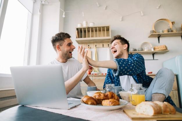 Amigos alegres que aplauden las manos que se sientan delante de la tabla con el desayuno y el ordenador portátil