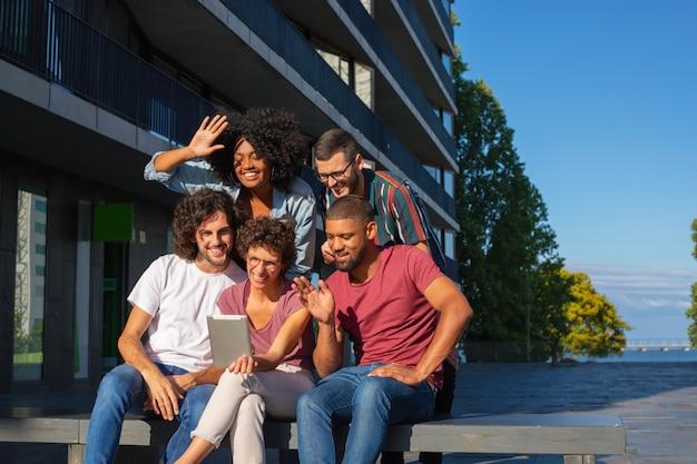 Amigos alegres que usan la aplicación de videoconferencia