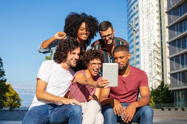 Amigos alegres que usan tableta para videollamadas grupales