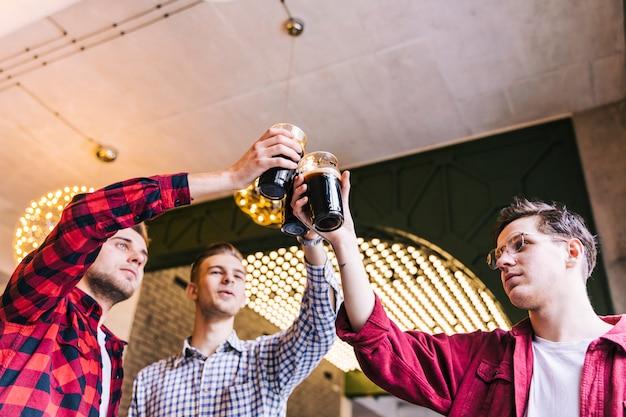 Amigos alegres tintinear vasos en bar