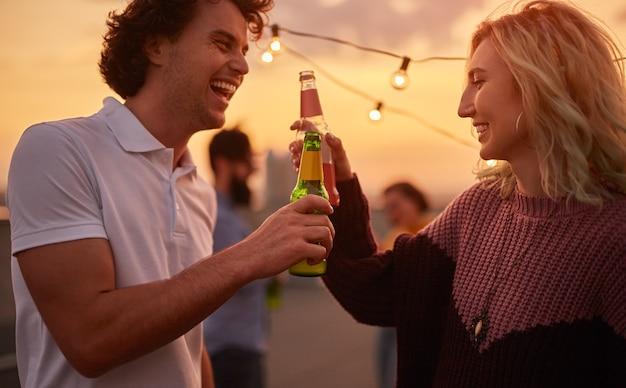 Amigos alegres tintineo con bebidas durante la fiesta