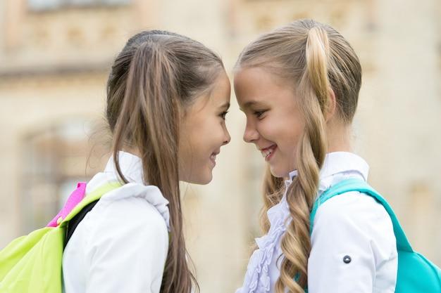 Amigos del alma gemela. las pequeñas colegialas visten uniforme escolar. lindas colegialas con largas colas de caballo que se ven encantadoras. finalización del año escolar. colegialas inteligentes alegres. colegialas felices al aire libre.