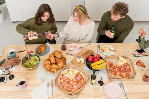 Amigos de alto ángulo comiendo en casa