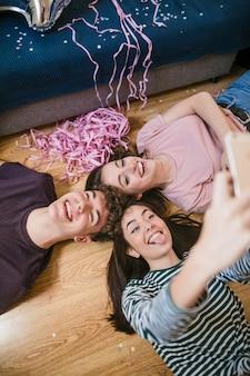 Amigos de alto ángulo tomando una selfie en el piso