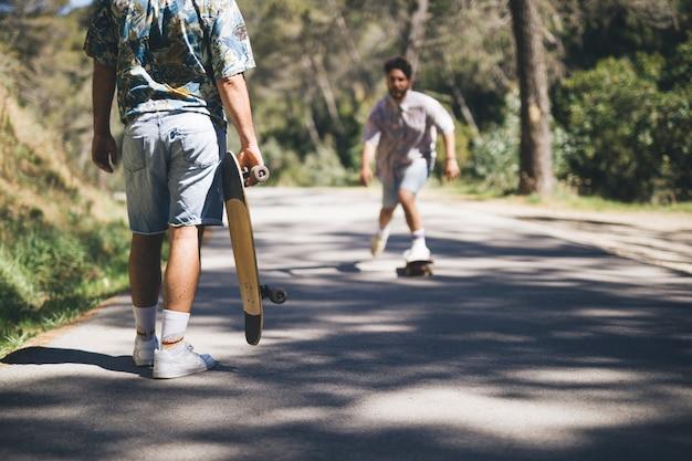 Amigos andar en monopatín en el camino forestal