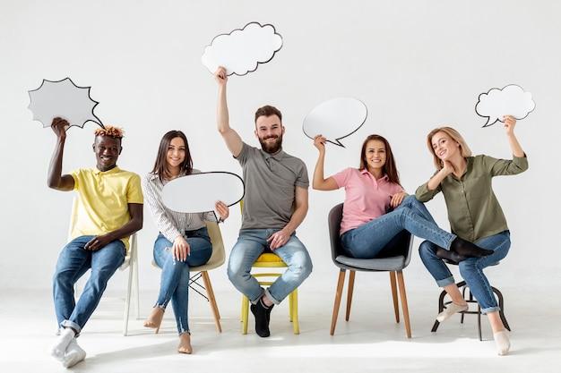 Amigos de ángulo bajo en sillas con burbujas de chat