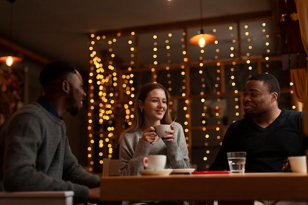 Amigos de ángulo bajo tomando café