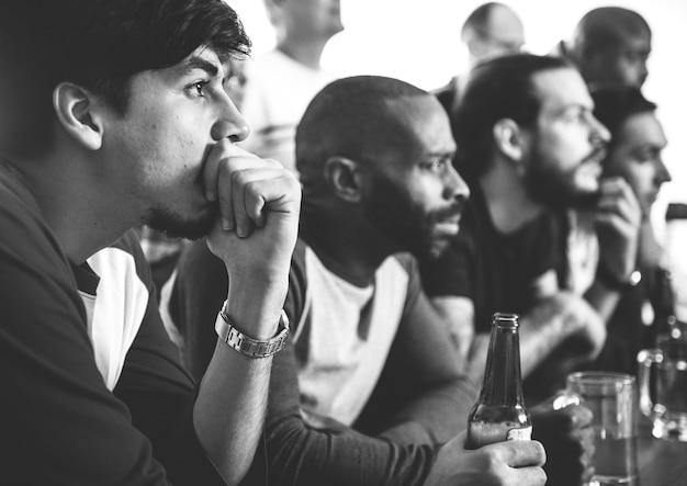 Amigos animando deporte en el bar juntos