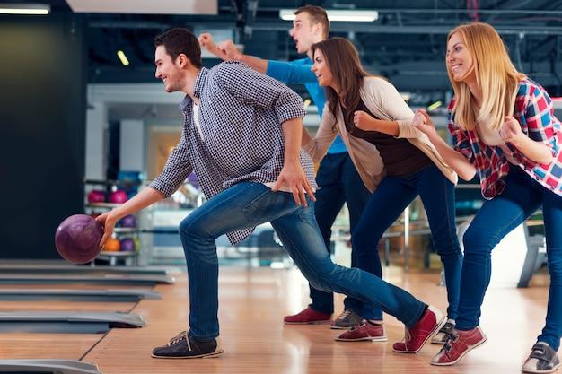 Amigos animando a su amigo mientras lanza una bola de boliche