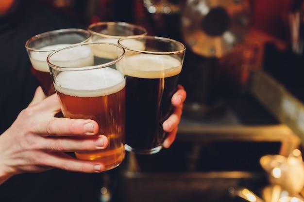 Amigos animando con vasos de cerveza sentados alrededor de la mesa de la cafetería - grupo de personas multirraciales que tuestan y tintinean las bebidas en la salud de los demás dentro del pub - aspecto vintage nostálgico de los viejos tiempos.