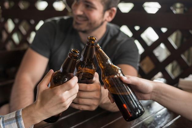 Amigos anónimos que tintinean botellas y mesa de bar