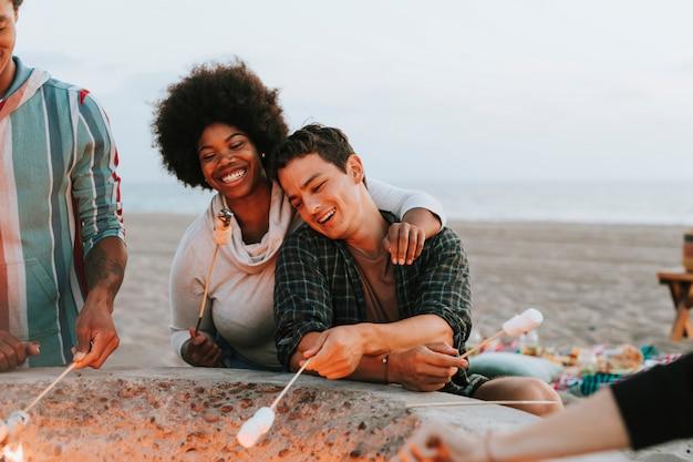 Amigos asando malvaviscos en la playa