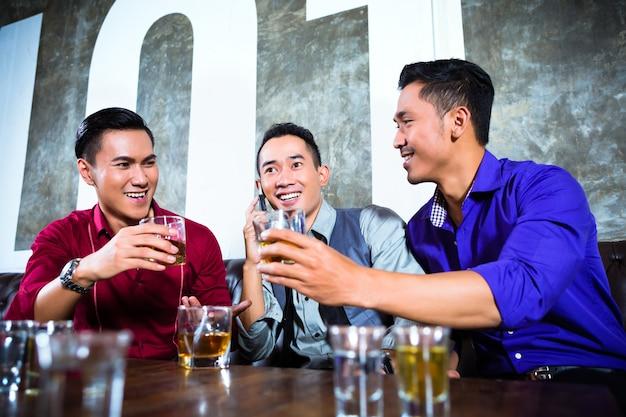 Amigos asiáticos bebiendo chupitos en discoteca
