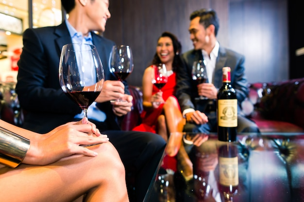 Amigos asiáticos bebiendo vino en el bar