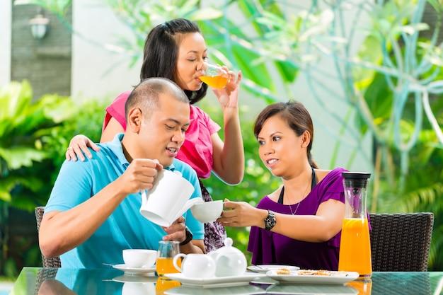 Amigos asiáticos tomando un café en el porche de casa