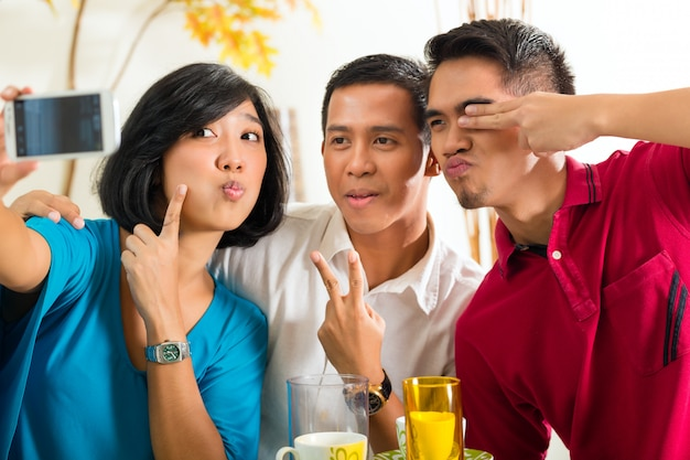 Amigos asiáticos tomando fotos con el teléfono móvil