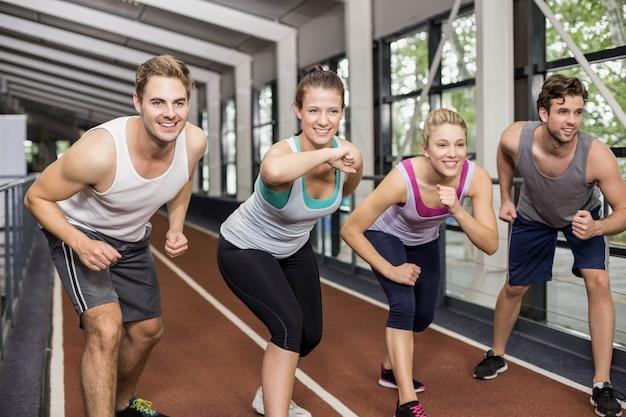 Amigos atléticos sonrientes van a comenzar a correr en la pista