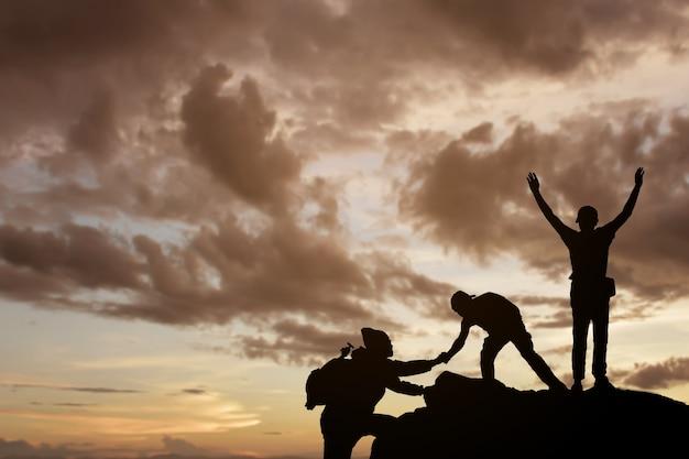 Amigos ayudándose unos a otros y con el trabajo en equipo tratando de llegar a la cima de las montañas