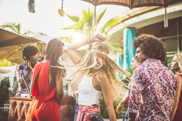 Amigos bailando en un lounge bar, con dj set