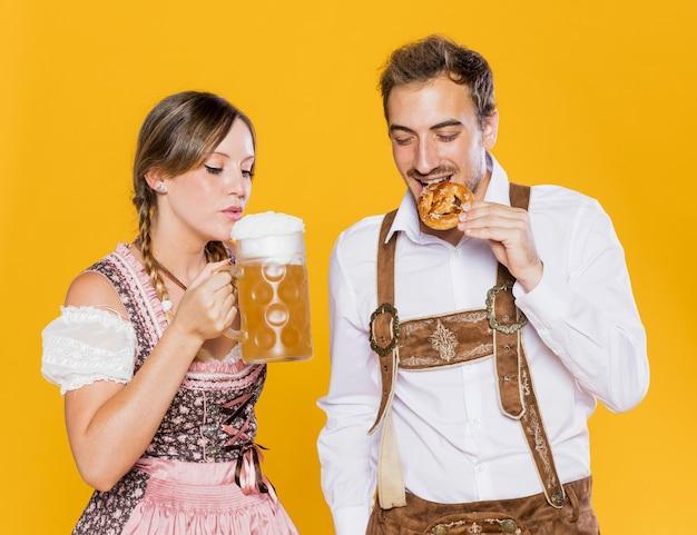 Amigos bávaros que prueban bocadillos de la oktoberfest