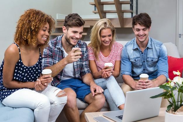 Amigos con bebidas mirando en la computadora portátil mientras está sentado en el sofá
