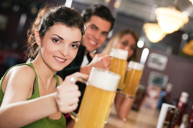 Amigos bebiendo cerveza en el bar