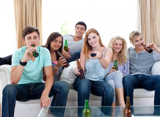 Amigos bebiendo cerveza en casa y viendo la televisión