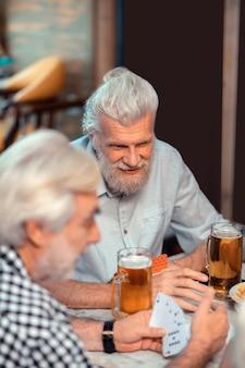 Amigos bebiendo cerveza. dos viejos amigos se sienten alegres mientras beben cerveza y juegan