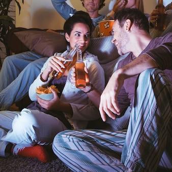Amigos bebiendo cerveza y haciendo una noche de película