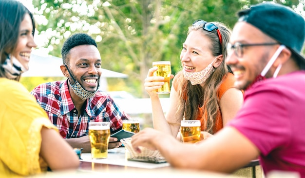 Amigos bebiendo cerveza con mascarillas abiertas: enfoque selectivo en el hombre izquierdo