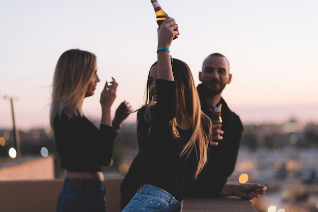 Amigos bebiendo cerveza en el techo