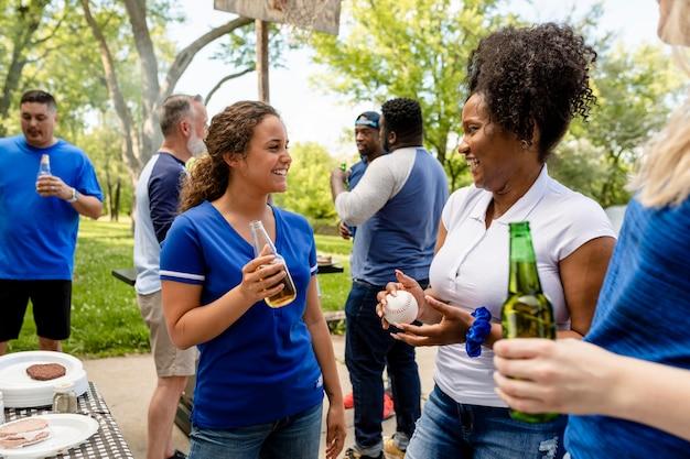 Amigos bebiendo y comiendo en una fiesta en el portón trasero