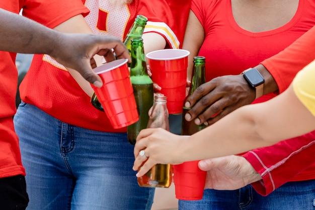 Amigos bebiendo en una fiesta en el portón trasero