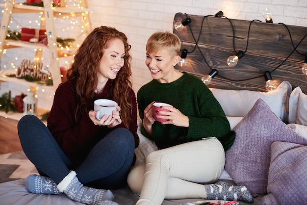 Amigos bebiendo té y hablando en el dormitorio