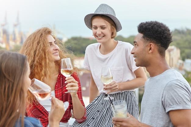 Amigos bebiendo vino y cócteles juntos