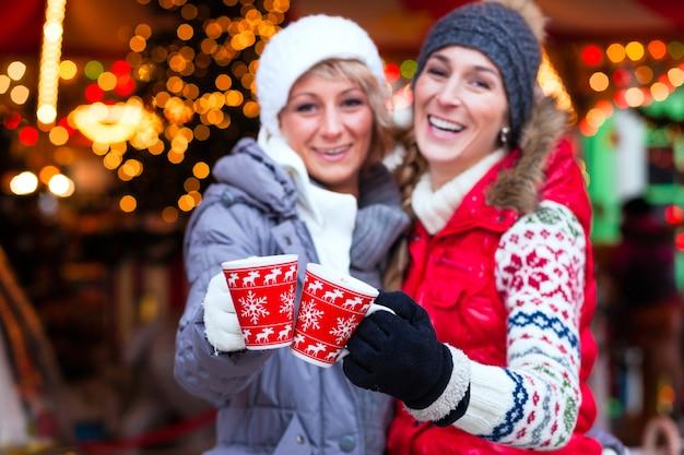 Amigos bebiendo vino especiado en el mercado navideño