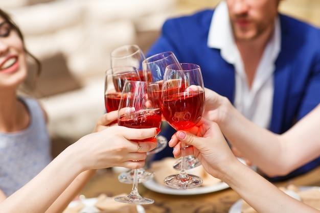 Amigos bebiendo vino en la terraza de verano