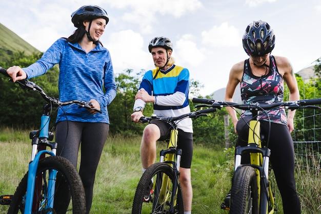 Amigos en bicicleta juntos en el campo.