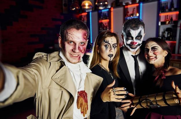 Amigos con bomba en las manos está en la fiesta temática de halloween con disfraces y maquillaje aterrador.