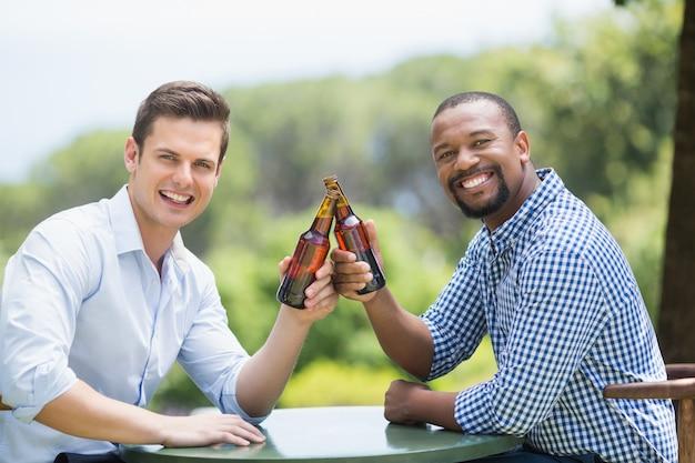Amigos brindando botellas de cerveza en el restaurante