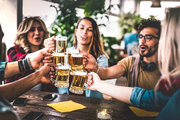 Amigos brindando cerveza en el bar de la cervecería interior en la fiesta de la azotea