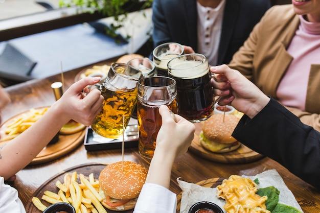 Amigos brindando con cerveza en restaurante