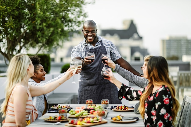 Amigos brindando con el chef en una fiesta de verano