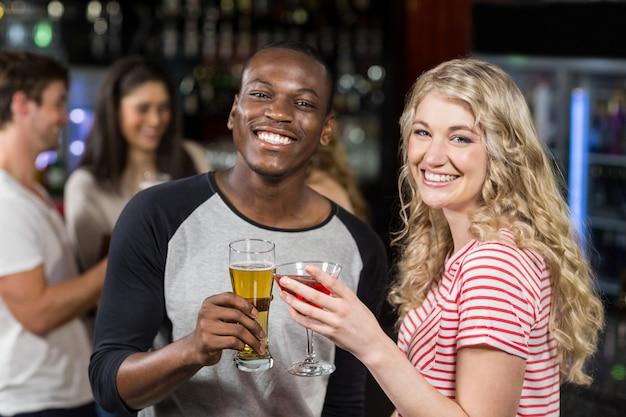Amigos brindando con cóctel y cerveza