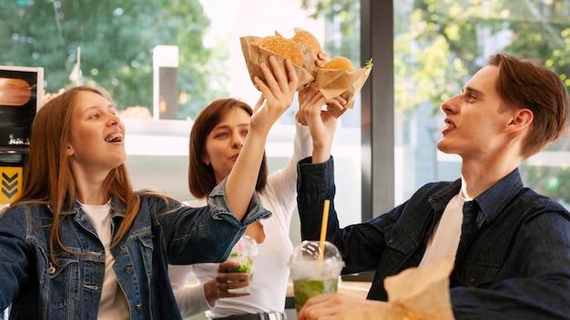 Amigos brindando con hamburguesas