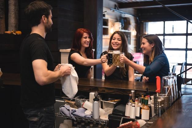 Amigos brindando con vasos de cerveza en la barra de bar
